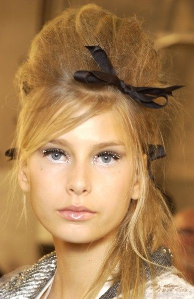 Messy beehive hairdo with black bow but really, the white pearlescent eyeliner is what is drawing our attention!