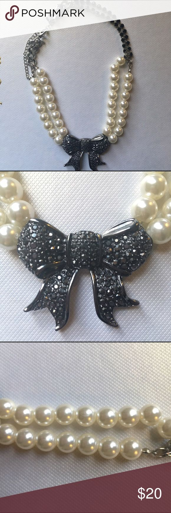 """Pearl necklace with rhinestone bow Adjustable pearl necklace with black rhinestone bow. The back has a clasp with adjustable 3"""" of length. The style of the necklace is short . The 1st pic is the shortest length. Very last picture is the longest length. Shortest length w/out clasp: 15"""" Longest length w/out clasp: 18"""" Express Jewelry Necklaces"""