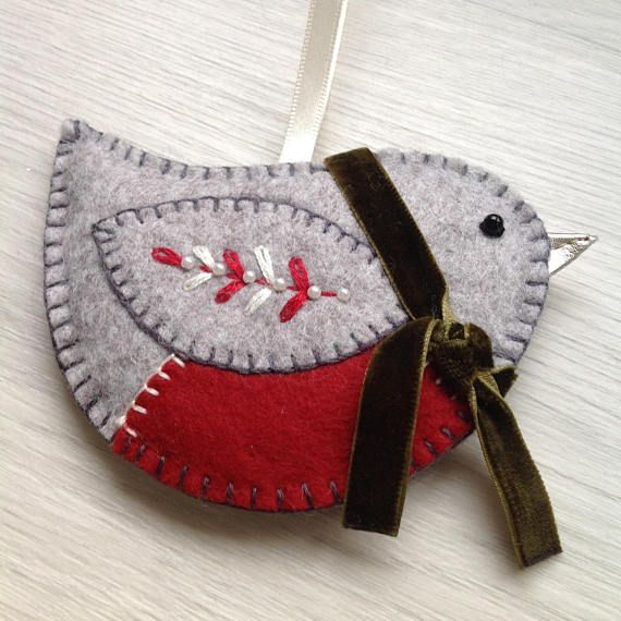 This cute little fella will look cute as a festive button on your Christmas Tree. He is made from pale grey felt with a big red tummy, and wears an olive velvet scarf to keep out the chills. The robin is hand cut and the decoration is hand embroidered and embellished with love. It is