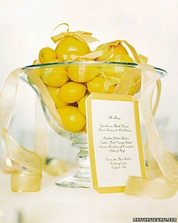 Lemons and grapefruits tied in yellow taffeta ribbons and piled into a glass compote make a bright, casual arrangement. The bows are secured by pins, and sheer yellow organdy drapes from the bowl. A coordinating menu card is trimmed with taffeta ribbon.
