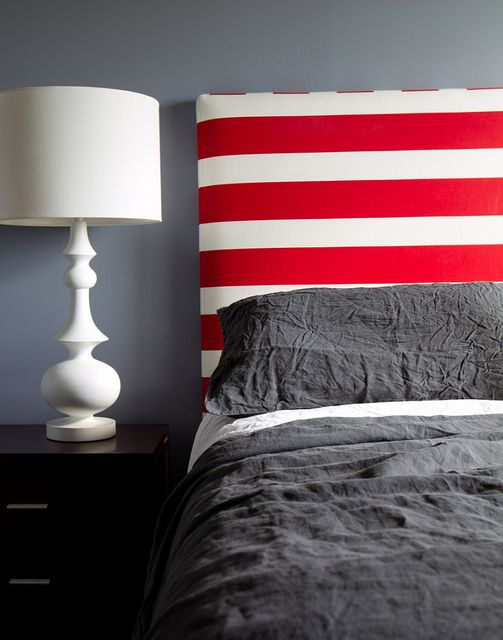 Nautical style bedroom with blue-grey walls and striped headboard. Fun for a boy's room!