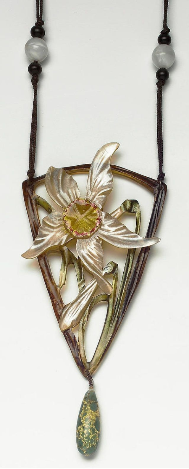 An Art Nouveau carved horn pendant necklace, by Elizabeth Bonté, circa 1900. A Carved Horn Pendant Necklace in the form of Narcissi coloured white, green and yellow, within a triangular framework, with mottled green and yellow glass pendant bead, the cord with matching and opalescent white beads pendant 10cm long, signed on reverse. #Bonte #ArtNouveau #pendant #necklace