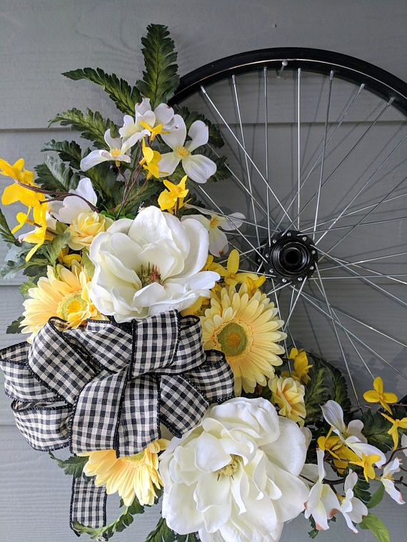 This unique Bicycle Wheel wreath is the perfect all-season accent for your home! A 17 black bicycle wheel serves as the base of this one-of-a-kind wreath. It is decorated with greenery, white magnolias, yellow daisies, small yellow roses, other faux florals, and features a black