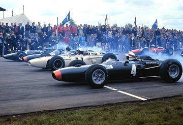 Silverstone, 1965. The green drops with Jackie Stewart's B.R.M. nearest the camera, then Richie Ginther's Honda, Graham Hill's B.R.M. and Jim Clark's Lotus, with the Ferrari of John Surtees in the second row.