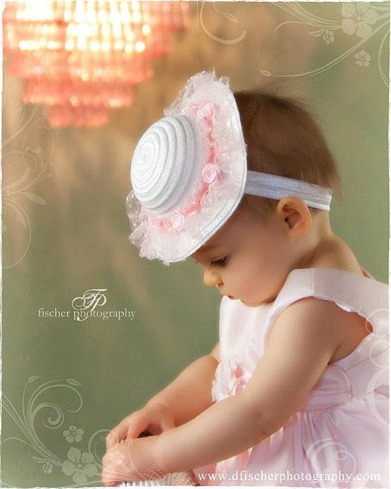 I bet you can buy a dolls hat and glue it into a head band to make this yourself.