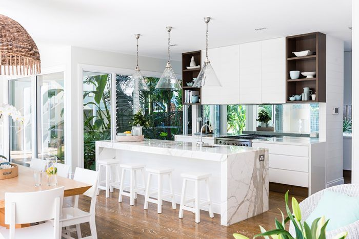 White marble and a sleek mirrored splashback make this a light and airy kitchen design. Photo: Steve Ryan. http://www.queenslandhomes.com.au/real-home-boat-house/