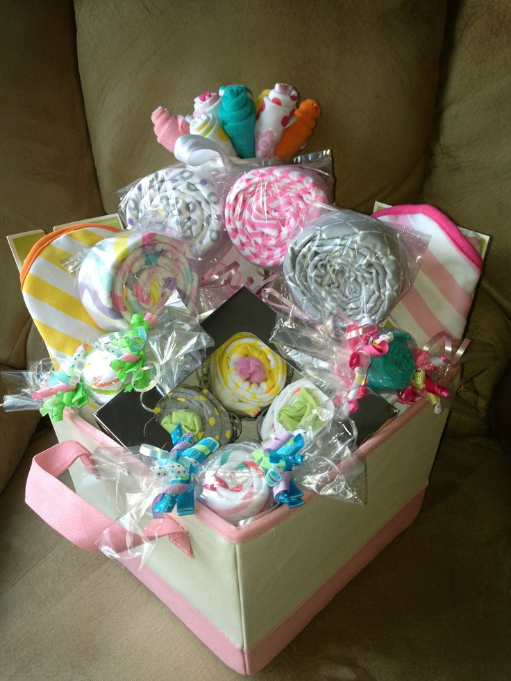 Baby shower basket with lollipop receiving blankets, washcloth bouquet, washcloth candies with hair clip bows and onesie cupcakes.