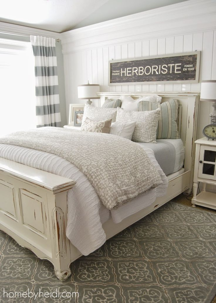 Cottage bedroom idea   white paneled headboard wall  Master bedroom perfect for a lake house or at the beach  Distressed cream headboard and footboard
