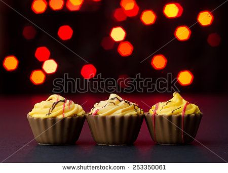 Chocolate Cup Cake over black table with red lights bokeh in the background
