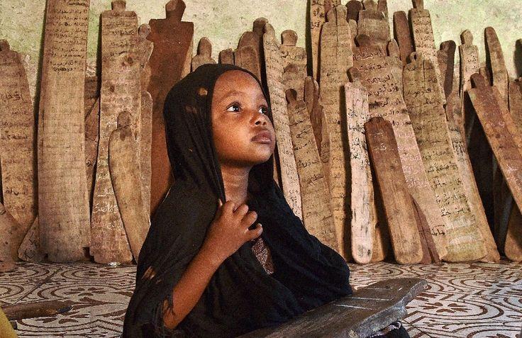 Una niña en una 'madrasa' o escuela coránica rodeada de tablas de madera con versos del Corán, el Mogadiscio el 25 de marzo de 2015Una niña en un...