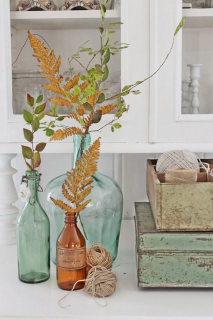 Seafoam colored glass bottles as vases for natural twigs leaves. Rustic yet modern. Comfortable.