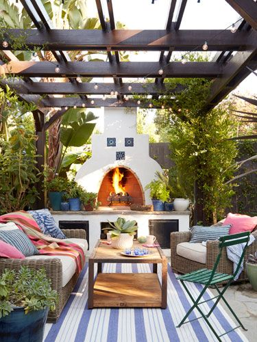 A vine-wrapped pergola illuminated by cafe lights enhances the romance, while boxy gray wicker seating offers contrasting shape, color, and texture.