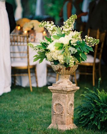 Large urns overflowing with floral arrangements give an outdoor wedding an elegant