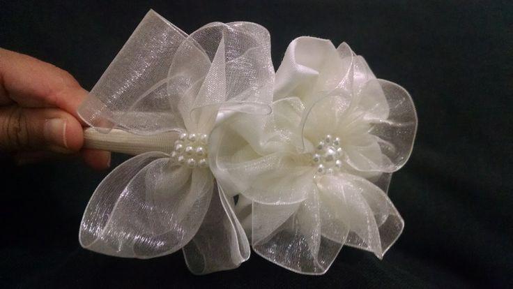Tiara com laço de organza e flor de cetim com organza. Acabamento feito com perolas aplicadas a linha.