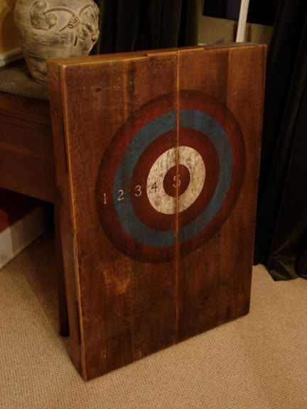 Vintage dart board cabinet on left wall after sofa and side table and in line with dividing lane between fire are and TV watching section.