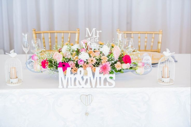 Monte Vista Venue large silver rose boat with mixed flowers in, a MR & MRS sign inside the flowers as well as in front of the boat and two small white birdcages with gold candles in it for a pink and gold wedding