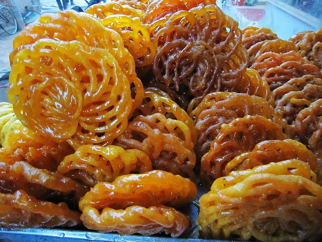 Street sweet, Jalebi -     Kathmandu, Nepal.  Made by deep-frying a wheat-flour (Maida flour) batter in pretzel or circular shapes, which are then soaked in sugar syrup.  The sweets are served warm or cold. They have a somewhat chewy texture with a crystallized sugary exterior coating. Citric acid or lime juice is sometimes added to the syrup, as well as rosewater or other flavours such as kewra water.