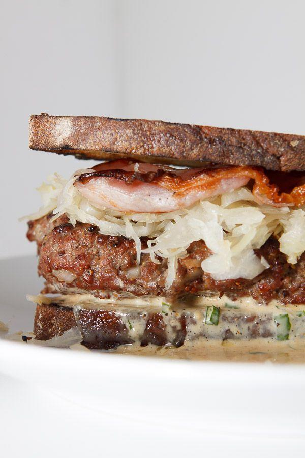 Zeit für einen Klassiker! Adaption des berühmten Reuben-Sandwiches als Burger: The Reuben Burger mit Sauerkraut, Mayonnaise und Graubrot. REZEPT Zutaten für den Reuben Burger (Für 4 Burger): 450g Rinderhackfleisch aus der Schulter 4 Scheiben Pancetta (Ersatzweise Schwarzwälder Schinken) 2 TL grober Senf 1/2 Zwiebel 1 Knoblauchzehe Salz, Pfeffer 1 kleine Dose Sauerkraut 4 Scheiben Schweizer Emmentaler 8 Scheiben Graubrot Für die Sauce: 125ml Mayonnaise 2 EL Schmand 1 1/2 EL Tomatenketchup 1…