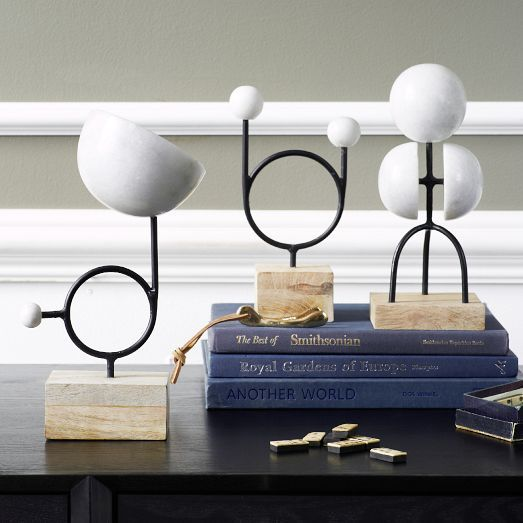 Abstract orbs sit atop an iron and wood base in the Moon Series, which was inspired by the lunar phases. Arrange them with plants, books and photographs for a sophisticated shelf or desk display.