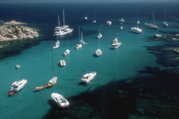 August 1984: A fleet of yachts at anchor off the sunny Mediterranean island of Cavallo, Corsica. by Slim Aarons/Getty Images