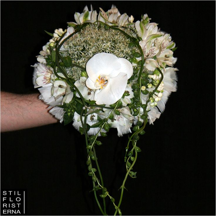 Annorlunda och något vild brudbukett i vitt, med en ringform i hållare, toppad med vit orkidé.
