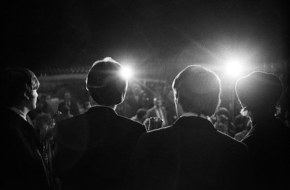 This photo shows a view of what the Beatles would see if they were entering a stage to perform for a crowd.  In my opinion this is a very surreal photograph because it shows a view that is not often experienced by those who are sitting in the audience.  This endorphin fueling view is not often experienced by most people in general, and that is the entire reason this photograph strikes me so much, mostly because of my past band experience.