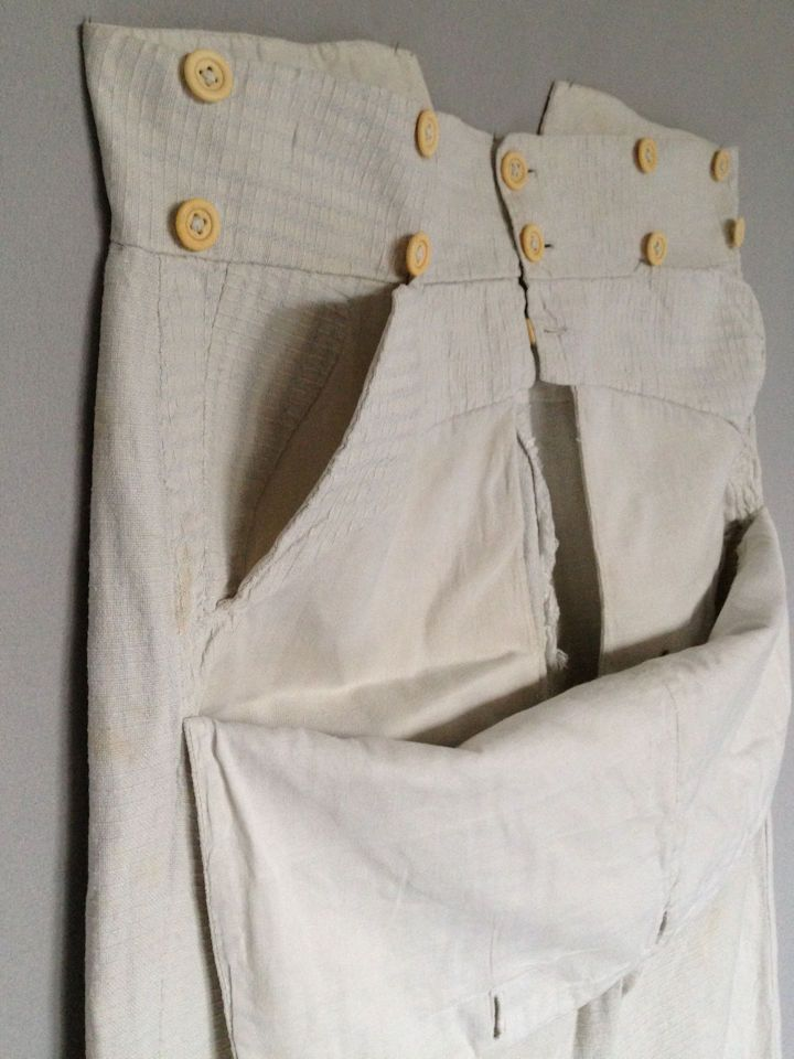 Men's Trousers Early 19th c Decorative textured cotton woven with a small dash motif. Description The wide waistband with a double row of five ivory bone buttons, fall front with five bone buttons a further button centre front, two large pockets, the full width flap with five buttonholes, wide legs at thighs tapering slightly and then straight, the back with deep V cutout, flanked by ivory bone buttons above a buckle and tab fastening, the top lined in cotton. waist 34 in  Meg Andrews…