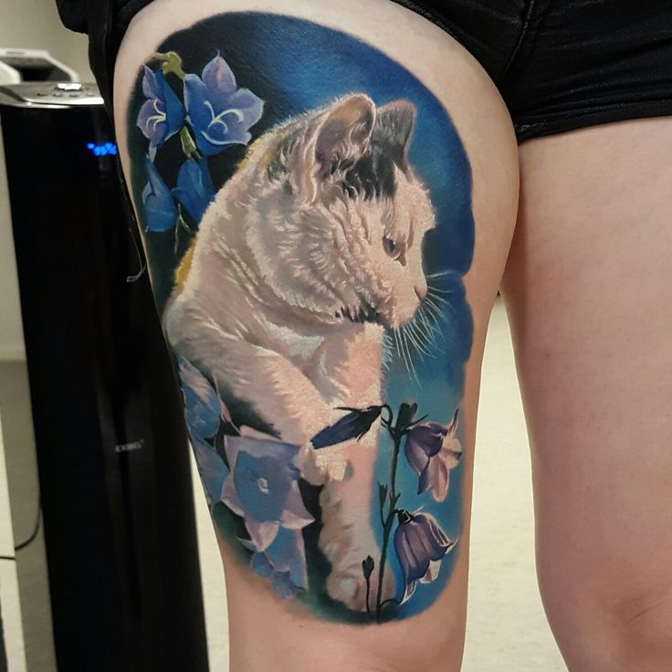Cat tattoo with flowers on thigh