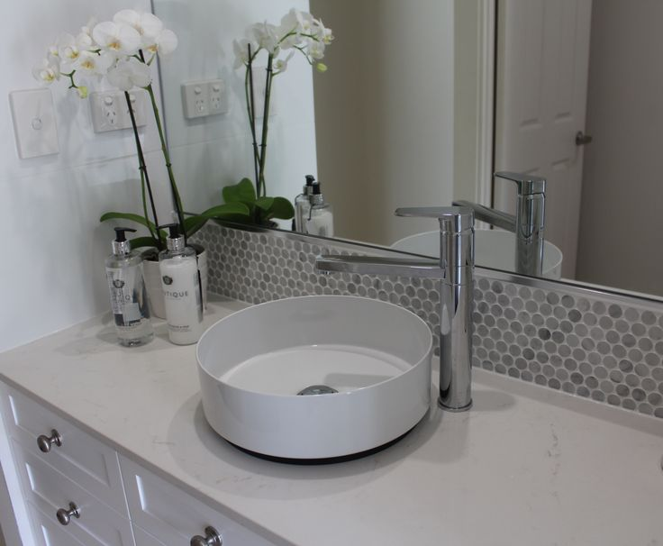 Frosty Carrina Ceaserstone Top. Carrara Penny Tile Border. White Shaker Vanity.