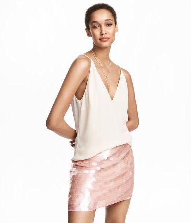 Puderrosa. En kort kjol i skir, vävd kvalitet med transparenta paljetter. Kjolen har dold dragkedja i sidan. Fodrad.