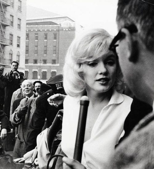 Marilyn Monroe surrounded by the press as she leaves a hospital in New York, 1961.