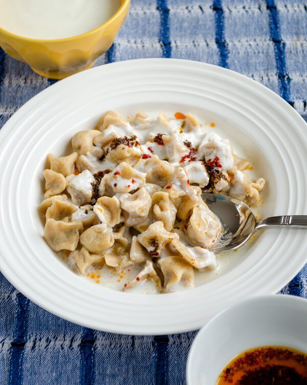 Turkish dumplings topped with garlicky yoghurt sauce and oil sauce with mint and paprika called manti are enough to make everyone hungry!