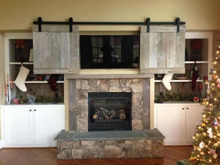 Sliding barn doors my Dad and I built out of reclaimed wood from his 1840's farmhouse to cover the television over the fireplace.
