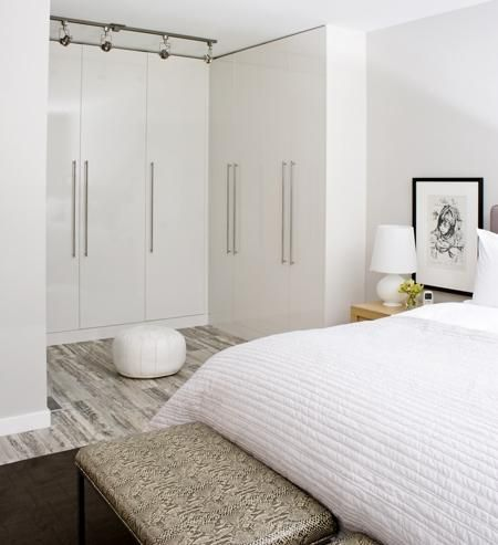 Here's a very modern bedroom with fantastic floors I must say. The closet is open to the bedroom but solid doors close off all of the clutter leaving a very white and bright modern space.