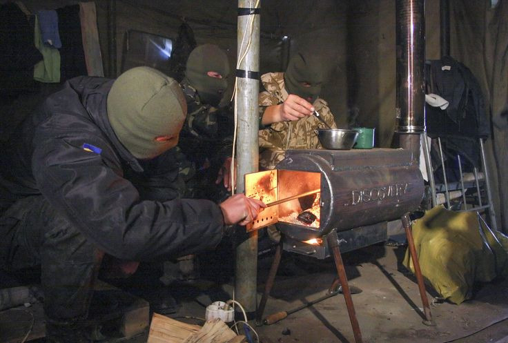 Ukrainian servicemen warm themselves in a tent with a moveable wood stove, given to them by volunteers, at a checkpoint near Mariupol, Ukraine. (epa/Photomig)