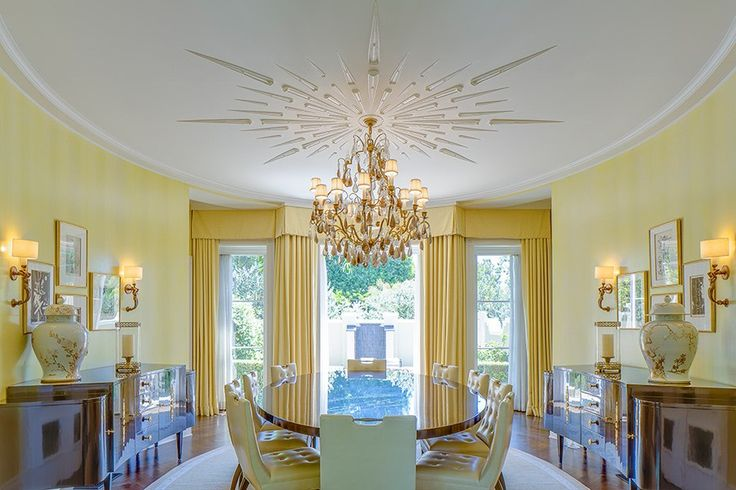 A sunburst-motif ceiling ornament is a focal point in the pale-yellow oval dining room.
