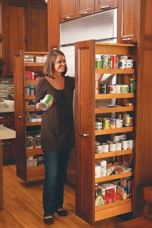 """Pull-out pantry: The tall cabinets, on either side of the refrigerator, hold canned goods, baking supplies and snacks."" from Taste of Home magazine:"