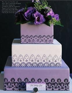 Gorgeous three tier square purple wedding cake with fresh flowers.