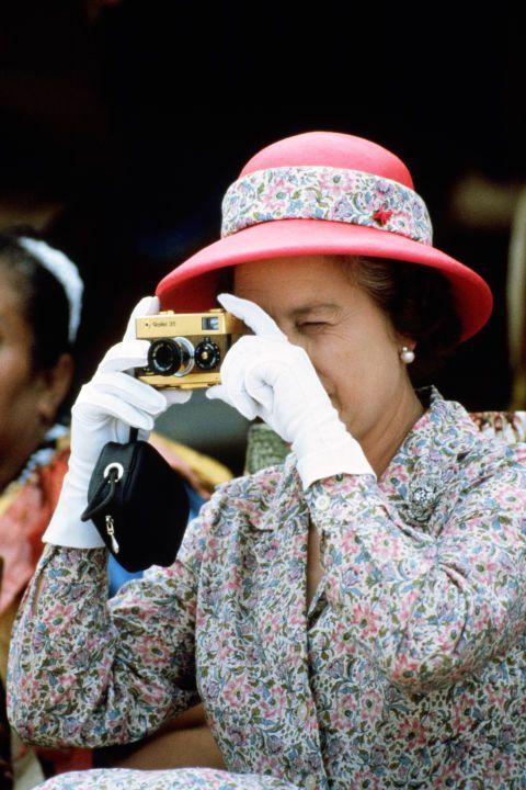 Queen Elizabeth in 1982 taking a photo.