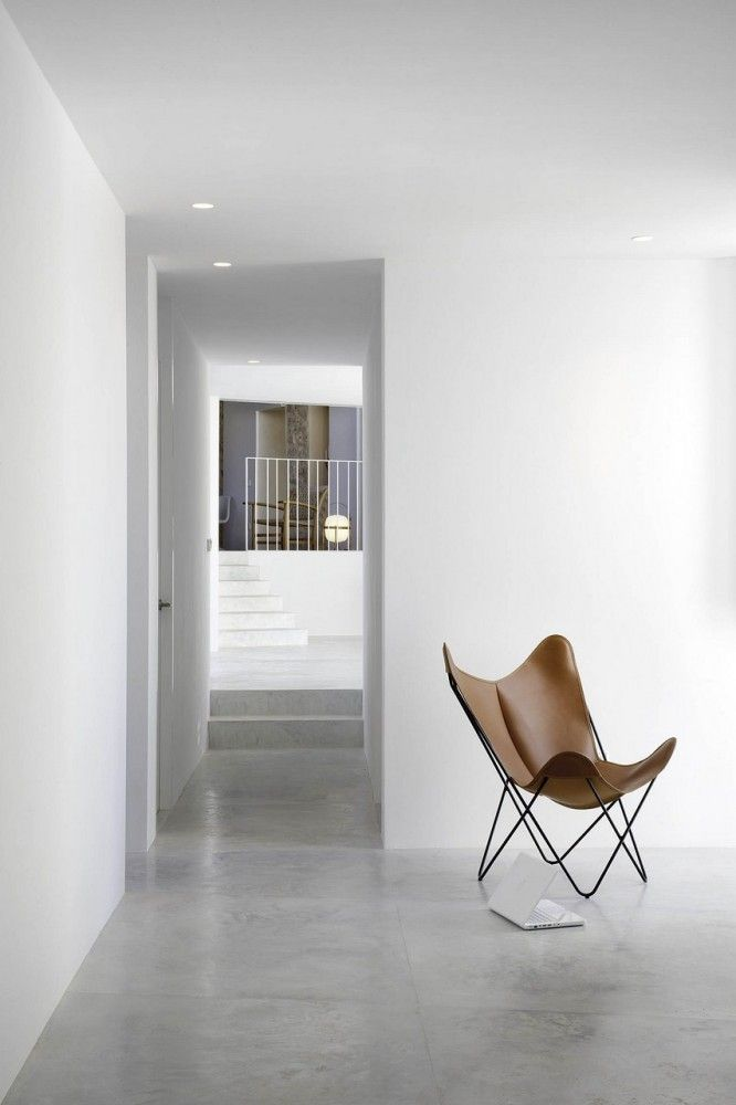 white walls, hallway, butterfly chair, cement floor