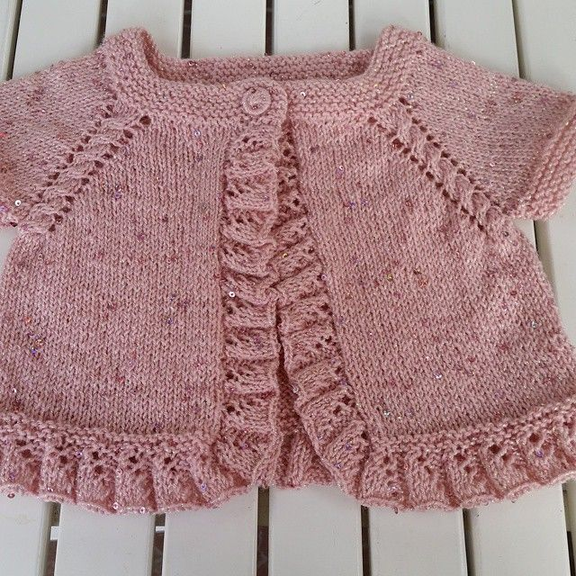 Pretty top-down pattern with cable on raglan line (increases at each side of cable) and sweet ruffles on front edges and hem. Lovely shade of pink, too.