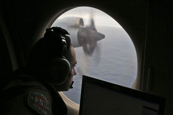 Flight officer Rayan Gharazeddine scans the water in the southern Indian Ocean off Australia from a Royal Australian Air Force AP-3C Orion during a search for the missing Malaysia Airlines Flight MH370, on March 22, 2014. (AP File Photo/Rob Griffith)