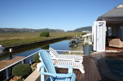 A decked walkway leads to the entrance of this impressive property for sale on Thesen Island, Knysna. Dining room with wood burning stove flows to open plan lounge with views, a large bar (with removable counter), covered verandah with built in braai and enclosed sun room