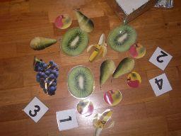 * Leg cijfers neer en gelamineerd plaatjes van fruit en laat de kinderen zelf een combinatie bedenken: 1 tros druiven, 2 bananen, 3 kiwi's etc.