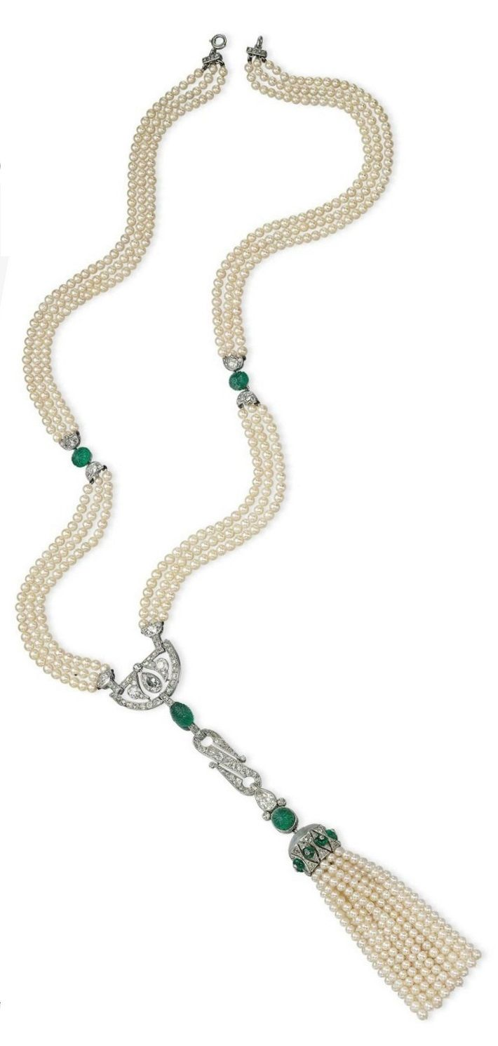 CARTIER - AN ART DECO PEARL, EMERALD AND DIAMOND SAUTOIR, CIRCA 1925. The three-strand pearl necklace, with carved emerald and diamond spacers, suspending a half-moon diamond-set openwork panel, a stylised S-shape link and a detachable pearl tassel with diamond, emerald bead and moonstone cap, with French assay mark for platinum, signed Cartier, numbered. #Cartier #ArtDeco #sautoir