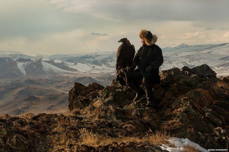 Irka Bolen on a mountain cliff edge with his eagle
