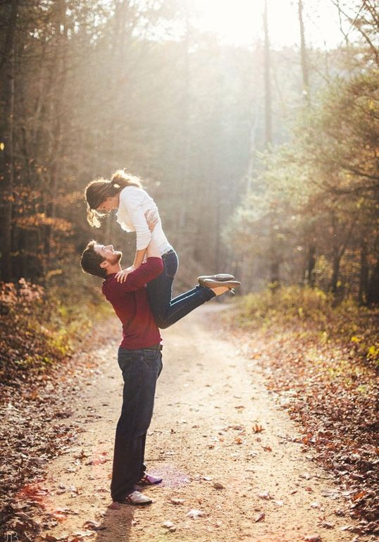 Fall engagement session with him lifting his fiance high into the air on a forest service road.