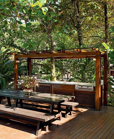 deck jardim copacabana: copa ampla e cheia fornece sombra para a mesa de refeições. Projeto