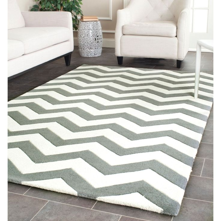 A contemporary chevron design and dense, thick pile highlight this handmade rug inspired by Moroccan patterns with today's updated colors. This floor rug has a dark grey background and displays stunning panel colors of ivory.