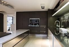 Moderne designkeuken Spatia van Arclinea. Deze strakke designkeuken van Arclinea komt uit de serie Spatia. Door de terugspringende plinten krijgt de keuken een licht en luchtig uiterlijk en lijkt hij te zweven. Het rvs keukenwerkblad geeft de keuken een moderne design uitstraling. De kastenwand van donker eiken fineer en het marmeren werkblad op het eiland geven de keuken warmte. Arclinea, foto Abe van Ancum